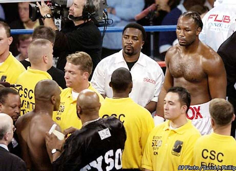 Mike Tyson, left, and Lennox Lewis look at each other across a line of security before their WBC/IBF heavyweight championship fight at The Pyramid in Memphis, Tenn., Saturday, June 8, 2002. (AP Photo/David J. Phillip) Photo: DAVID PHILLIP