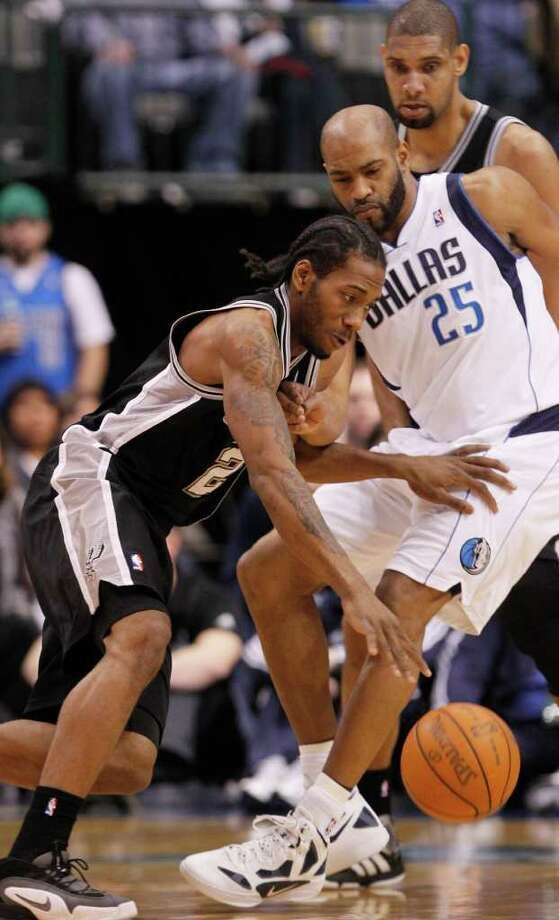 San Antonio Spurs forward Kawhi Leonard (2) dribbles past Dallas Mavericks guard Vince Carter (25) as Spurs center Tim Duncan watches during the first half of an NBA basketball game in Dallas, Sunday, Jan. 29, 2012. (AP Photo/LM  Otero) Photo: Associated Press