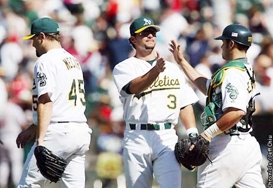 Eric Chavez, center, greets catcher Ramon Hernandez, right, after closer Jim Mecir struck out Craig Biggio to end the game as the A's beat the Houston Astros 5-1 in Oakland on Saturday afternoon. Photo by Jeff Chiu/The Chronicle Photo: Jeff Chiu