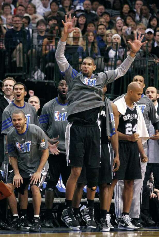 San Antonio Spurs center Tim Duncan raises his arms as he and fellow starter Tony Parker, left, watch from the bench with other teammates during overtime against the Dallas Mavericks in an NBA basketball game in Dallas, Sunday, Jan. 29, 2012. The Mavericks won 101-100. (AP Photo/LM  Otero) Photo: Express-News