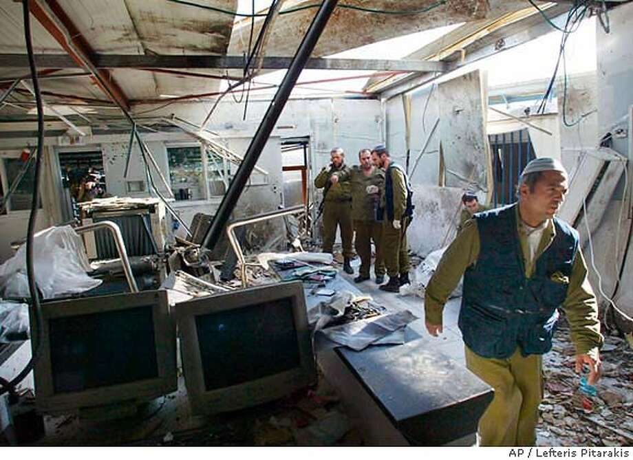 Israeli army officers and investigators collect evidence and remove debris at the scene of a suicide bomb attack at the Erez crossing terminal between Israel and the Gaza Strip Wednesday Jan. 14, 2004. A female Palestinian suicide bomber, mother of two children, blew herself up at the major crossing point between Israel and the Gaza Strip, killing four Israelis and wounding seven other people. (AP Photo/Lefteris Pitarakis) Photo: LEFTERIS PITARAKIS