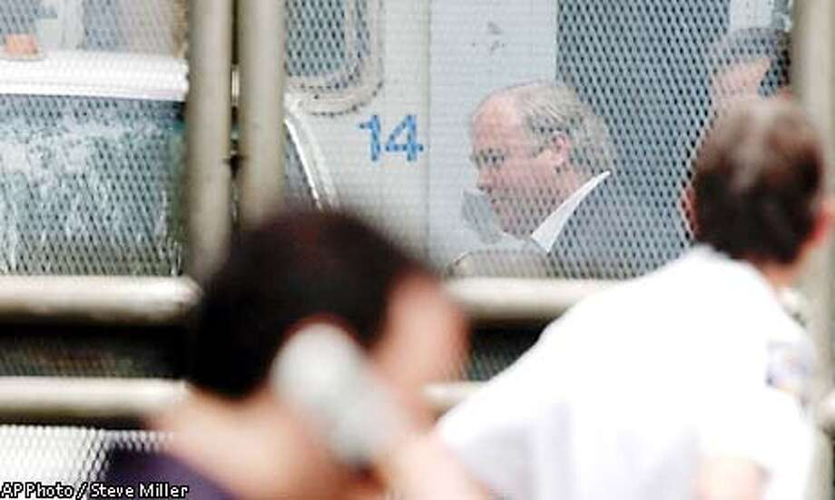Michael Skakel, behind the fence, is loaded into a van Friday, June 7, 2002, at the Norwalk Superior Court after he was found guilty of murder in the death in 1975 of Martha Moxley of Greenwich, Conn. Skakel was handcuffed after the verdict and led off immediately to jail. Sentencing was set for July 19. (AP Photo/Steve Miller) Photo: STEVE MILLER