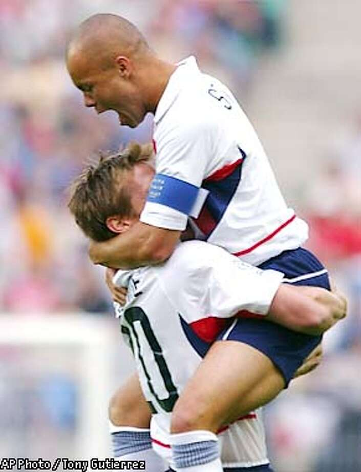 USA's Brian McBride, left, is hugged by team captain Earnie Stewart after striker Landon Donovan scored the second goal against Portugal in their Group D, 2002 World Cup soccer match at the Suwon World Cup Stadium in Suwon, South Korea, Wednesday, June 5, 2002. Also in the group are Poland and South Korea. (AP Photo/Tony Gutierrez) Photo: TONY GUTIERREZ