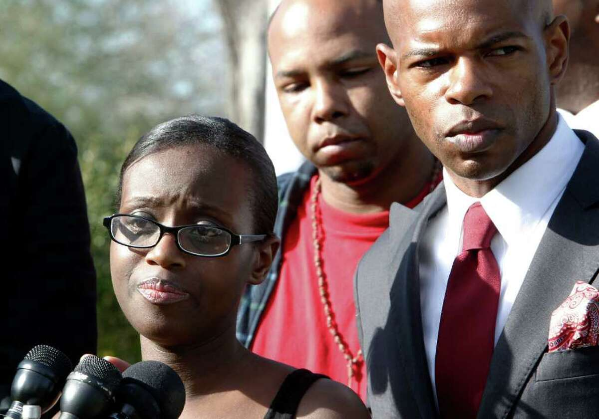 Annika Lewis addresses a news conference Sunday along with her husband, Sebastian Prevot, center, and activist Deric Muhammad. She said officers beat her when she used her phone to video her husband's arrest.