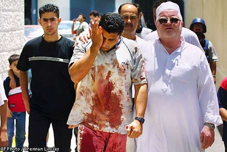 Palestinian Khaled el-Kharez is comforted by friends as he leaves the morgue, where his brother's body Tareq, 24, lies, who was killed by apparent stray Israeli gunfire, on the second day of a military incursion in the West Bank city of Nablus, Saturday, June 1, 2002. Dozens of tanks and armored vehicles swept into Nablus on Friday, effectively closing down the West Bank's largest city in its effort, says Israel, to hunt down militant Palestinians wanted by the Israeli Government. (AP Photo/Brennan Linsley) Photo: BRENNAN LINSLEY