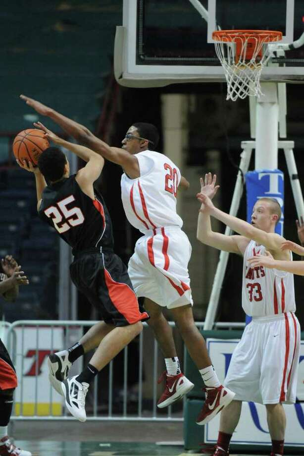 Albany Academy's Jelanie Currie blocks a shot by Long Island Lutheran's Anthony Pate, left,  during the 2012 Coaches Vs. Cancer High School Challenge at the Times Union Center on Sunday Jan. 29, 2012 in Albany, NY.  Academy's Matt Laclair is at right. (Philip Kamrass / Times Union ) Photo: Philip Kamrass / 00016239A