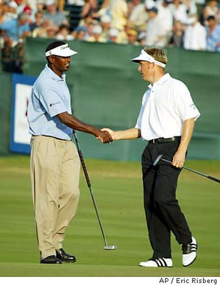 Stuart Appleby of Australia, right, is greeted by Vijay Singh, left, of the Fiji Islands on the 18th green of the Plantation Course after finishing the 3rd round of the Mercedes Championships in Kapalua, Hawaii Saturday Jan. 10, 2004. Appleby leads the tournament by two strokes after shooting a 7-under-par 66 to finish at total 20-under-par. Singh is in second place after shooting 4-under-par 69 to finish at total 18-under par.(AP Photo/Eric Risberg) Photo: ERIC RISBERG