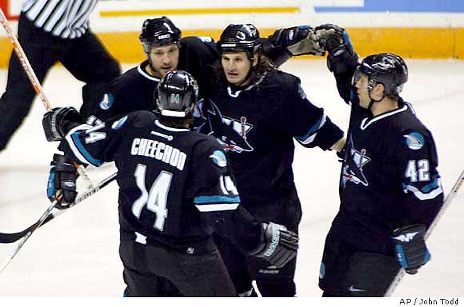The Sharks' Scott Thorton, left, is congratulated by teammates Mike Ricci, center, Tom Preissing, right, and Jonathan Cheechoo after scoring against the Blue Jackets in the first period. Associated Press photo by John Todd