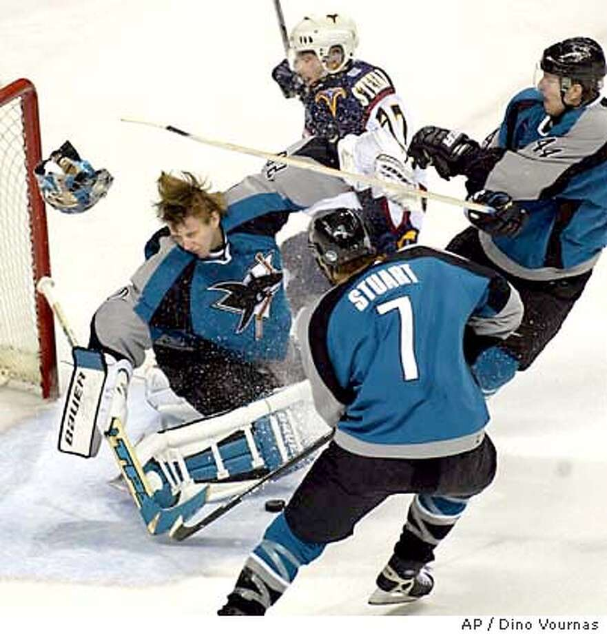 San Jose Sharks goalie Evgeni Nabokov of Kazakhstan loses his helmet after getting a stick to the head from teammate Christian Ehrhoff as the Atlanta Thrashers' Patrik Stefan of the Czech Republic, top, comes into the play during the first period Saturday, Jan. 10, 2004, in San Jose, Calif. Sharks defenseman Brad Stuart tries to clear the puck in the foreground. (AP Photo/Dino Vournas) Photo: DINO VOURNAS