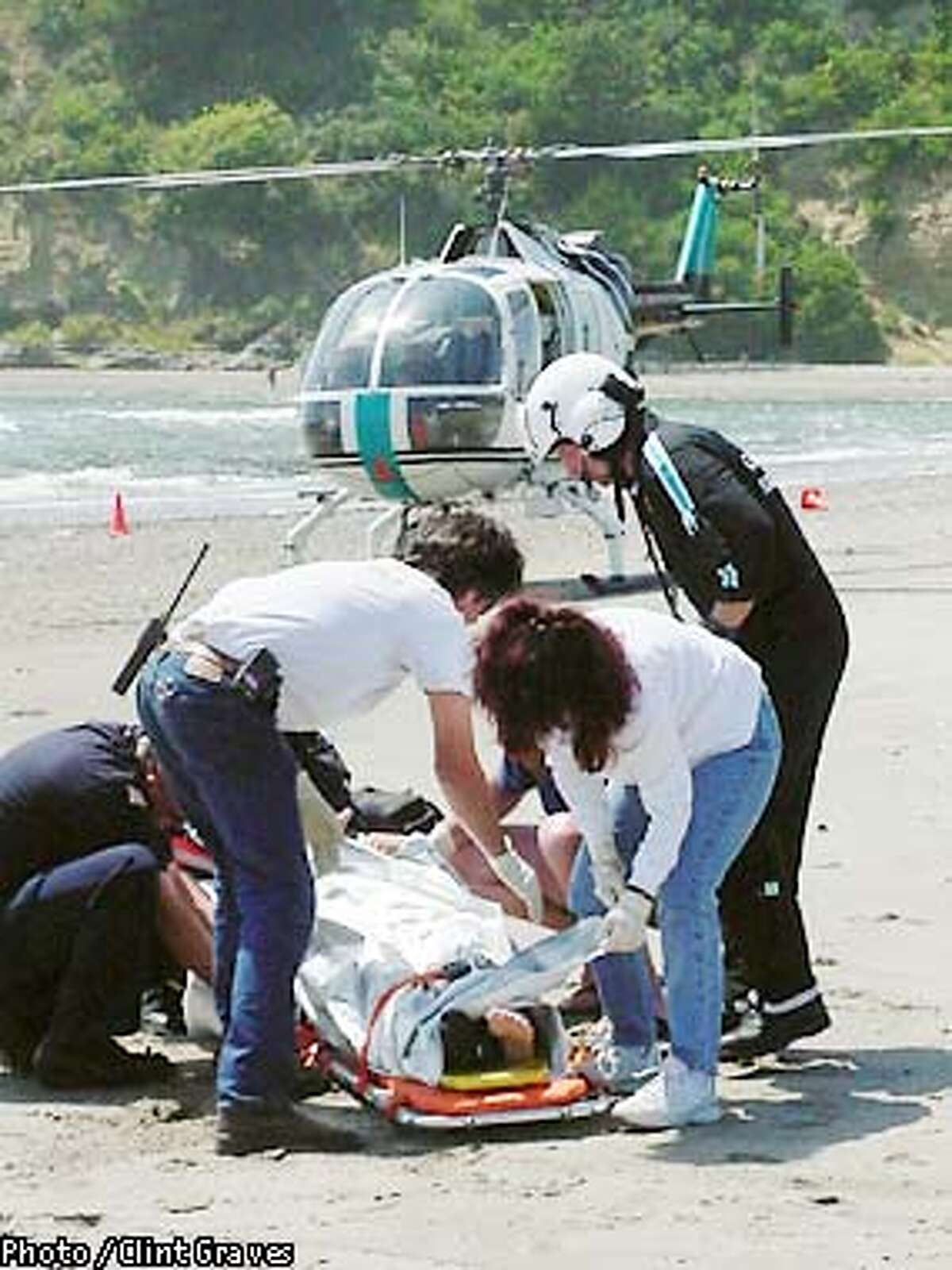 THIS IS A HANDOUT IMAGE. PLEASE VERIFY RIGHTS. Surfer and shark attack victim Lee Fontan being helped by, from left: Aaron Jarvis, Marin Co FD; Toby Bisson, Stinson Beach FD; Tommye (cq) Jarvis, Stinson Beach FD, and Eric Lewis, flight nurse with CALSTAR. Photo By Clint Graves/Special to the Chronicle.