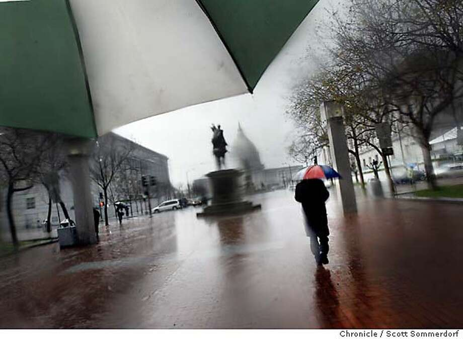 solnit084_ss  On a rainy day, a pedestrian walks westward through UN Plaza heading toward the Simon Bolivar statue and City Hall.  Scott Sommerdorf / The Chronicle  -----  UN Plaza is the heart of San Francisco according to essayist Rebecca Solnit. She sites the Simon Bolivar statue, The longitude/latitude markings in the concrete of the square, and as icons to what she feels when she is in this place. Scott Sommerdorf / The Chronicle Photo: Scs