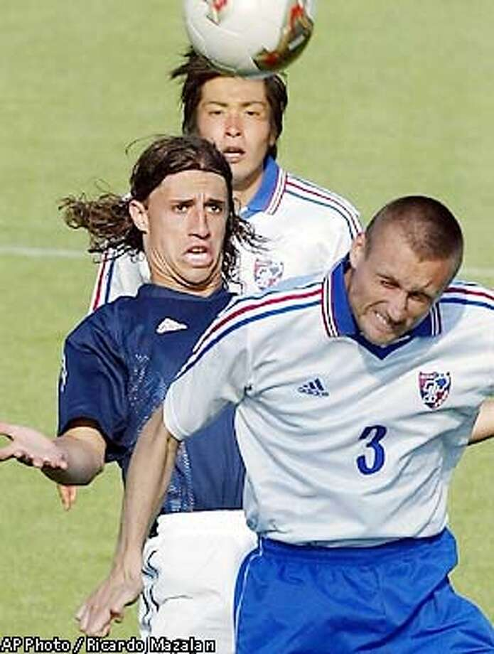 Sandwiched between F.C. Tokyo's Jean Carlo Witte, front, and one of his teammates, Argentina's forward Hernan Crespo, who plays for Italy's Lazio, jumps for the ball during a friendly match at Argentina's training site in Naraha, north of Tokyo, Tuesday, May 28, 2002. Argentina will play in the Group F with England, Sweden and Nigeria. (AP Photo/Ricardo Mazalan) Photo: RICARDO MAZALAN