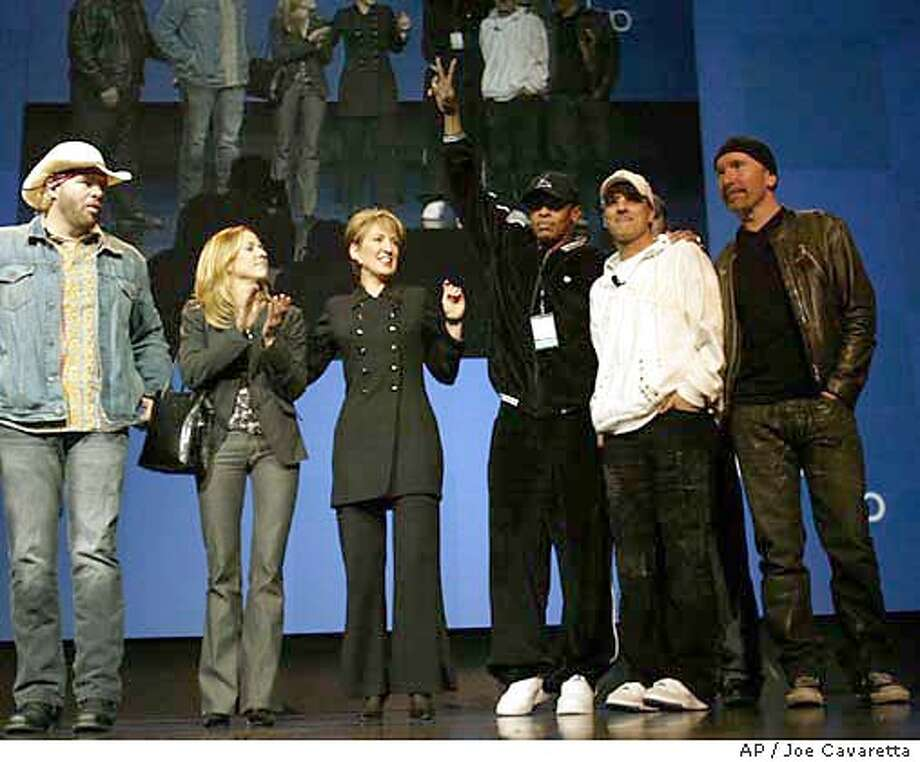 Toby Keith, left, Cheryl Crow, second from left, Carly Fiorina, Chairman and CEO of HP, third from left, Dr. Dre, fourth from left, record producer Jimmy Iovine, fifth from left, and Edge, from U2 appear together during a keynote address of the Consumer Electronics Show at the Las Vegas Convention Center Hilton Hotel Thursday, Jan. 8, 2004. The artists and the company spoke about stopping music piracy. (AP Photo/Joe Cavaretta) Photo: JOE CAVARETTA
