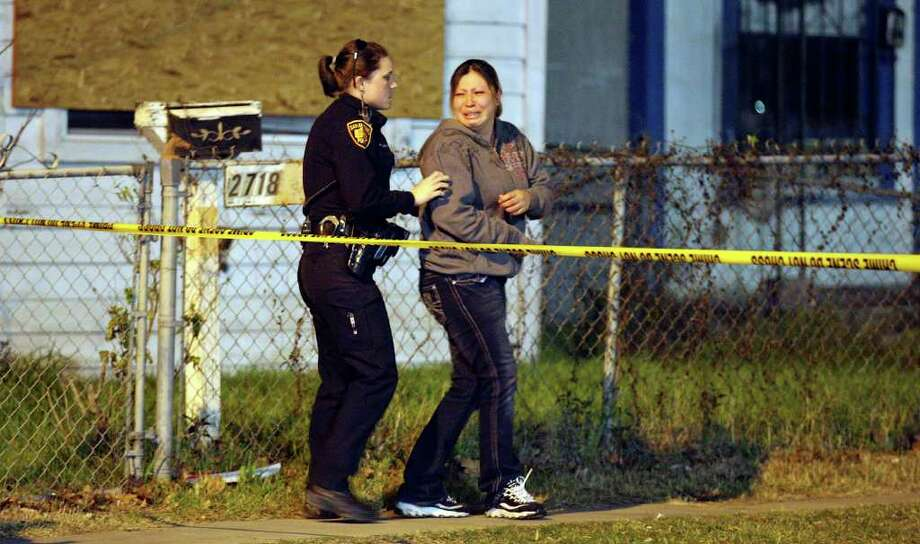 FOR METRO - A member of the SAPD escorts a relative of a man shot and killed, near the intersection of W. Commerce and N. Calaveras streets, from the scene Sunday Jan. 29, 2012. Photo: EDWARD A. ORNELAS, San Antonio Express-News / © SAN ANTONOI EXPRESS-NEWS (NFS)