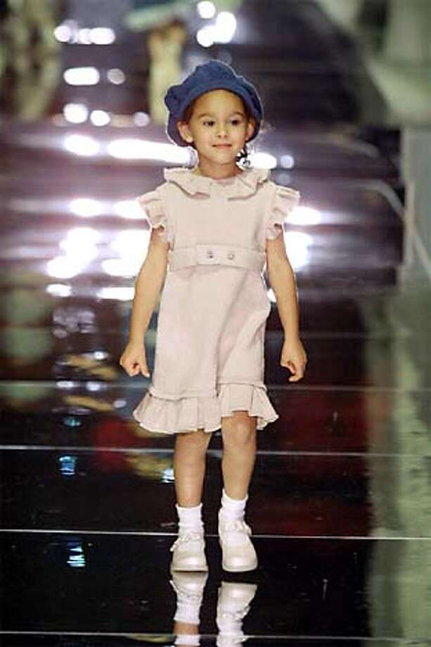 Petite style: Jacquelynn Wong sends a girl's ruffled wool dress down the runway at the Academy of Art College fashion show.