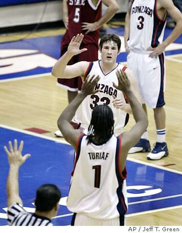 Gonzaga forward Cory Violette, center, is congratulated by forward Ronny Turiaf as he leaves the game against Washington State in the second half, Sunday, Dec. 28, 2003, in Spokane, Wash. Violette scored a career-high 31 points as Gonzaga won, 96-58.  (AP Photo/Jeff T. Green) Cory Violette high-fives Ronny Turiaf. The 6-foot-8 Violette and 6-10 Turiaf help clog the paint for the Bulldogs. Photo: JEFF T. GREEN