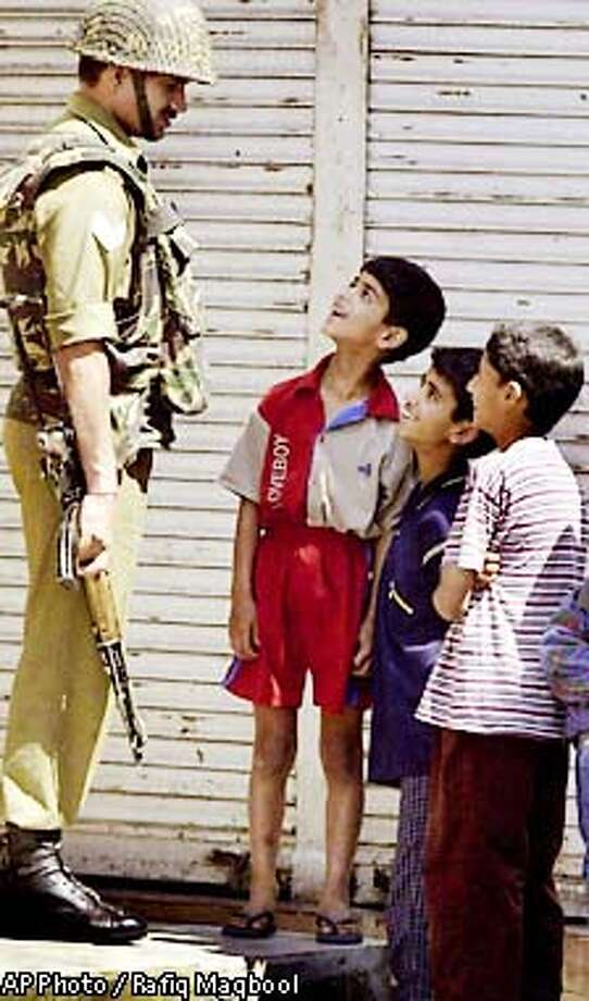 An Indian Border Security Force soldier takes time from his security post to chat with some local Kashmiri boys at Maisuma locality in Srinagar, India Friday, May 31, 2001. Security has been beefed up in the area after unidentified gunman down a Kashmiri shopkeeper. (AP Photo/Rafiq Maqbool) Photo: RAFIQ MAQBOOL