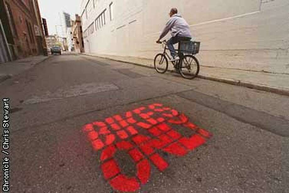 """Eric Berman, owner of the Tempest Bar at Mary and Natoma Streets, rides past a """"BIKES ONLY"""" sign, spray painted on the asphalt of Mary Street. SAN FRANCISCO CHRONICLE PHOTO BY CHRIS STEWART Photo: CHRIS STEWART"""