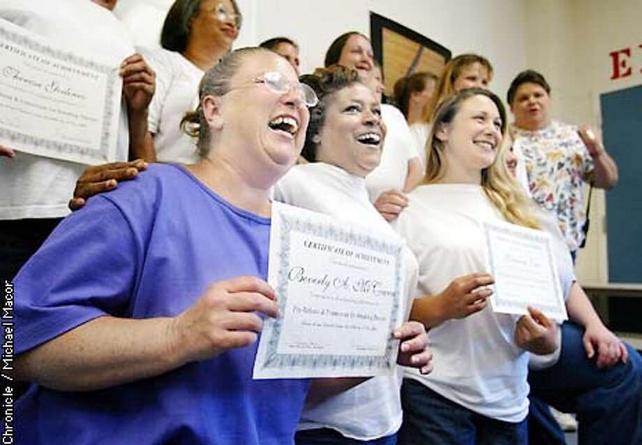"The graduating class of the ""Pre-Release & Framework for Breaking Barriers"" smiles for one final photograph. Inmates Beverly McCowen, (front left) Paulette Sylvester, (center) and Vanessa Tate, hold their diplomas. This may just be the very last class of it's kind at Chesney. McCowen and Sylvester are on a bus to Chowchilla May 30th. Leo Chesney Detention Facility for Women in the town of Live Oak is nearing it's end. Without a last minute reversal from Governor Gray Davis the prison will close down next month. by Michael Macor/The Chronicle Photo: MICHAEL MACOR"