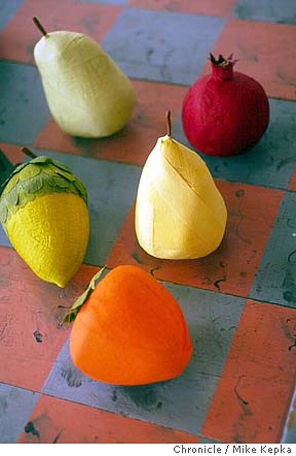 """ananda070028_mk.jpg Arnold's suprise balls come in an assortment of different shapes.  Anandamayi (cq) Arnold is a Berkeley artist who's specialty is making """"Surprise Balls"""" out of crepe paper. The balls, which take about 20 minutes to make on average, are filled with about 10 small toys and treats. Arnold sells most of her balls at a Berkeley store called Tail of the Yak. 12/24/03 in Berkeley MIKE KEPKA/The Chronicle Photo: MIKE KEPKA"""