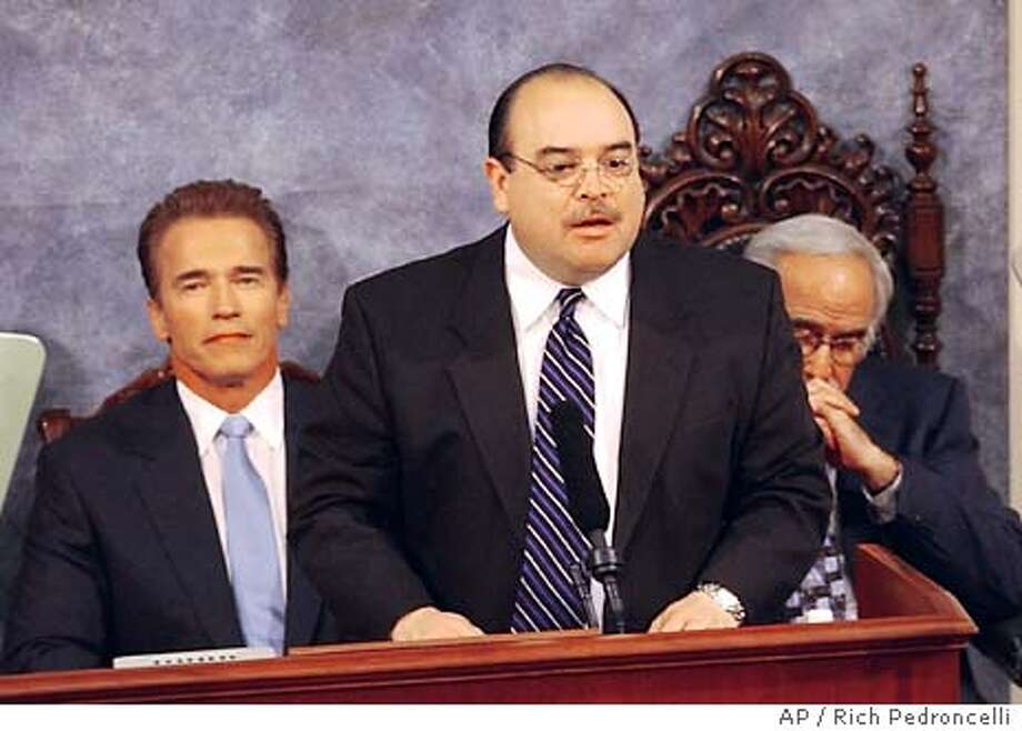 The California Fair Political Practices Commission announced, they had filed suit, Wednesday, Jan. 7, 2004, against Lt. Gov. Cruz Bustamante, center, for taking campaign funds above the legal limit during last years recall election. The suit alleges that Bustamante, seen introducing Gov. Arnold Schwarzenegger, left, during Tuesday's State of the State Address, took $3.8 million above the state's legal campaign limits from Indian tribes during the recall race against Schwarzenegger and other candidates. Bustamante could face a maximum potential fine of $9 million. Also seen is State Sen. President Pro Tem John Burton, D-San Francisco, right. (AP Photo/Rich Pedroncelli) Photo: RICH PEDRONCELLI