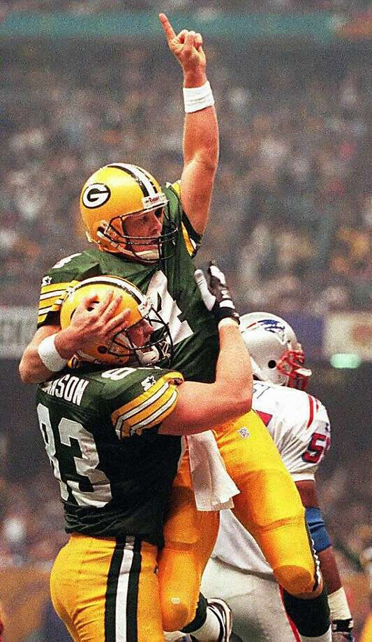 NEW ORLEANS, UNITED STATES:  Green Bay Packers quarterback Brett Favre (C) is hoisted in the air by teammate Jeff Thomason (L) after Favre ran for a touchdown to give Green Bay a 27-14 lead over the New England Patriots in the second quarter of Super Bowl XXXI at the Louisiana Superdome in New Orleans, Louisiana 26 January. Patriots linebacker Todd Collins is rear right. (Photo credit should read DON EMMERT/AFP/Getty Images) Photo: Don Emmert
