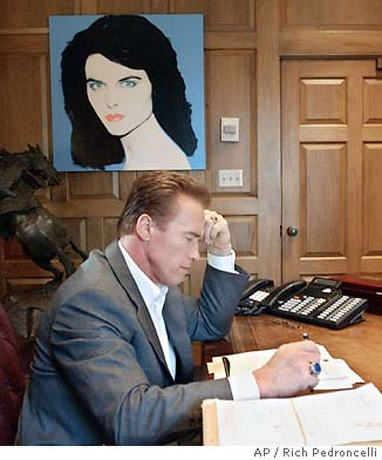 Gov. Arnold Schwarzenegger looks over some papers in his private office at the Capitol in Sacramento, Calif., Monday, Jan. 5, 2004. Schwarzenegger will deliver his first State of the State address to a joint session of the Legislature Tuesday, Jan. 6, 2004. He is expected to outline his plans to balance the budget. (AP Photo/Rich Pedroncelli) Photo: RICH PEDRONCELLI