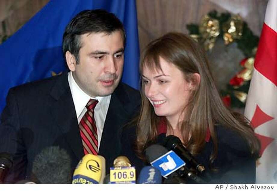 Top presidential candidate Mikhail Saakashvili, left, speaks to his wife Sandra Roelofs during a news conference in Georgia's capital Tbilisi, Sunday, Jan. 4, 2004. Six weeks after President Eduard Shevardnadze's dramatic resignation in the face of mass demonstrations, Georgians on Sunday voted for his successor, widely expected to be Mikhail Saakashvili, the man who led the protests. (AP Photo/Shakh Aivazov) Photo: SHAKH AIVAZOV