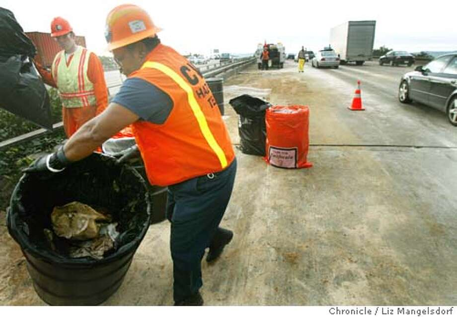 Joseph Brown, with Consolidated Waste Industries, moves a barrel that contains some of the waste that was cleaned up on Highway 101 near Grand Ave after an oil spill closed freeway lanes for hours. Brown, with the help of Nigel Hull, background left, are near the end of the clean-up process, with only one lane of Southbound Highway 101 still closed (spill is on southbound lanes). (this photo is taken a little before 10am, with the spill happening hours earlier)  Liz Mangelsdorf/ The Chronicle Photo: LIZ MANGELSDORF