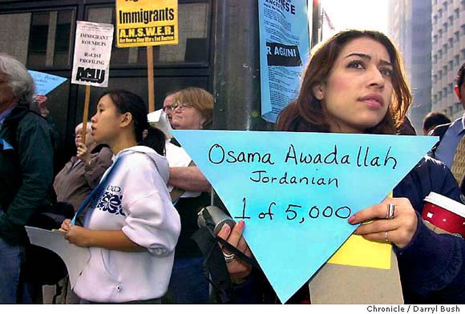 Supporter Alaleh Kianerci of San Francisco, right holds a blue triangle with the name of one of the many people who were claimed to have been deported by the U.S. government according to the Blue Triangle Network, as activists hold a demonstration on Washington Street accross the street from the Bureau of Immigration and Customs Enforcement to protest many of U.S. policies targeting Arab-Americans as well as the Patriot Act. Supporter Jean Pak of Davis , CA, is background left (white top). 11/19/03 in San Francisco. DARRYL BUSH / The Chronicle Photo: DARRYL BUSH