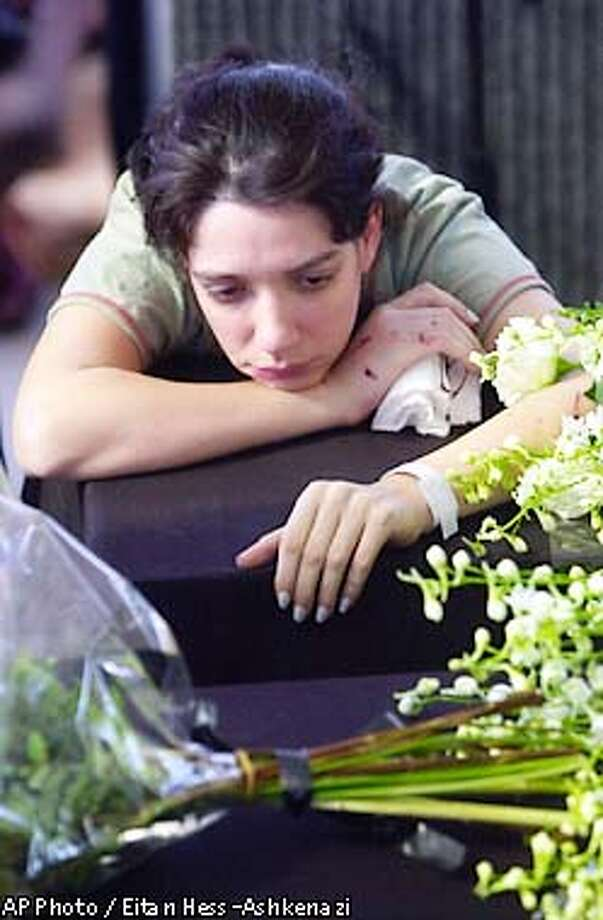 Chen Kenaan the mother of Sinai, 18-month-old, and the daughter of Ruth Peled, 56, leans on their coffins during their funeral in Kibbutz Shfayim of Tel Aviv Wednesday, May 29 2002. Ruth Peled and her 18-month-old granddaughter Sinai Kenaan were killed Monday as a Palestinian suicide bomber blew himself up in the city of Petach Tikvah near Tel Aviv. (AP Photo/Eitan Hess-Ashkenazi) Photo: EITAN HESS-ASHKENAZI