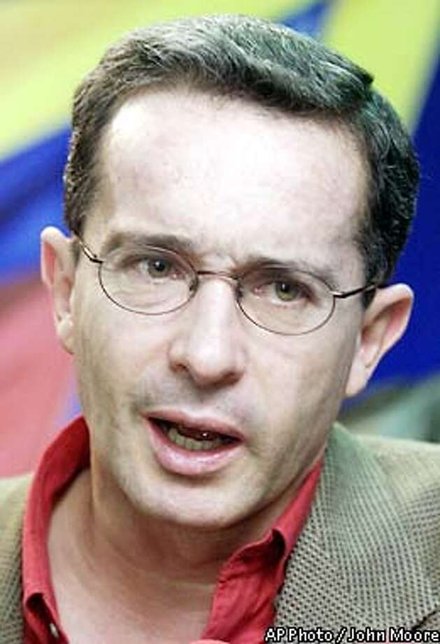 Presidential candidate Alvaro Uribe speaks to the press in Bogota Sunday, May 19, 2002 on the final day of campaigning ahead of the May 26 presidential vote. Uribe leads in the polls going into Sunday's presidential election. (AP Photo/John Moore) Photo: JOHN MOORE