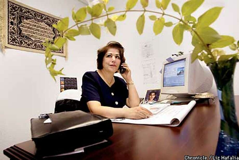 Nayer Rahimi is an Iranian immigrant who was approved for citizenship in 1998 but has had to wait until this month for the oath ceremony. She is at her workplace, Century 21 as a realtor, framed by a jasmine plant from her garden.  (PHOTOGRAPHED BY LIZ HAFALIA/THE SAN FRANCISCO CHRONICLE) Photo: LIZ HAFALIA