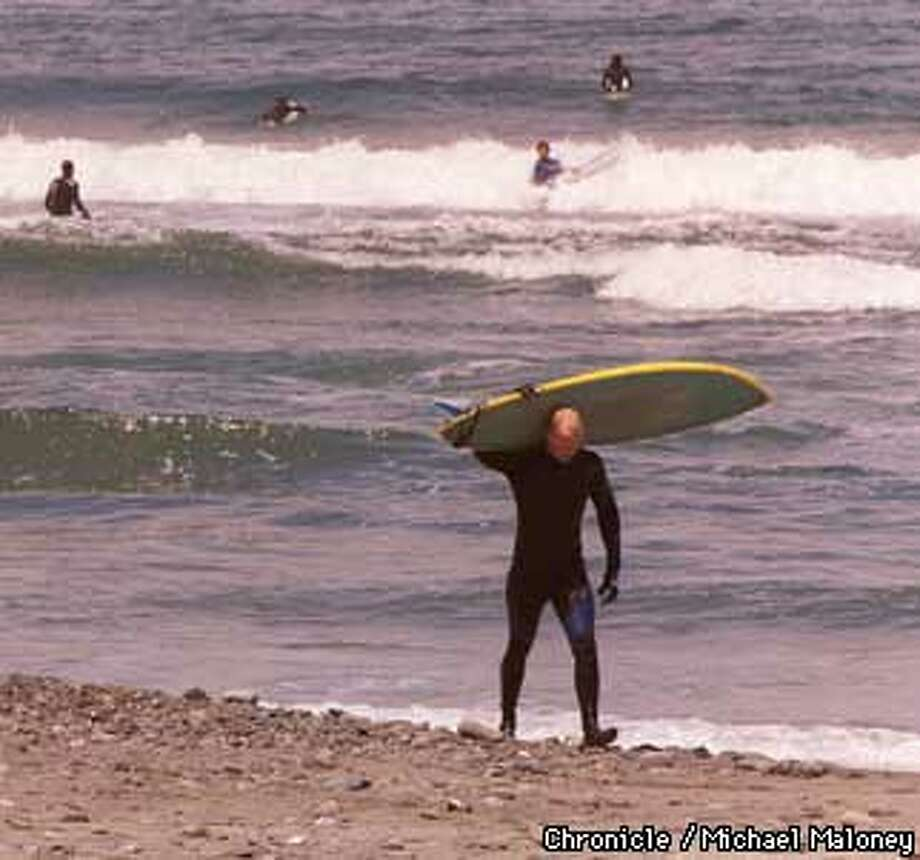 A surfer walks along Linda Mar State Beach in Pacifica - a popular surf spot.  The Pacifica city council voted last night to prohibit changing clothes in the parking lots of the popular Pacifica surf beaches.  Photo by Michael Maloney Photo: MICHAEL MALONEY