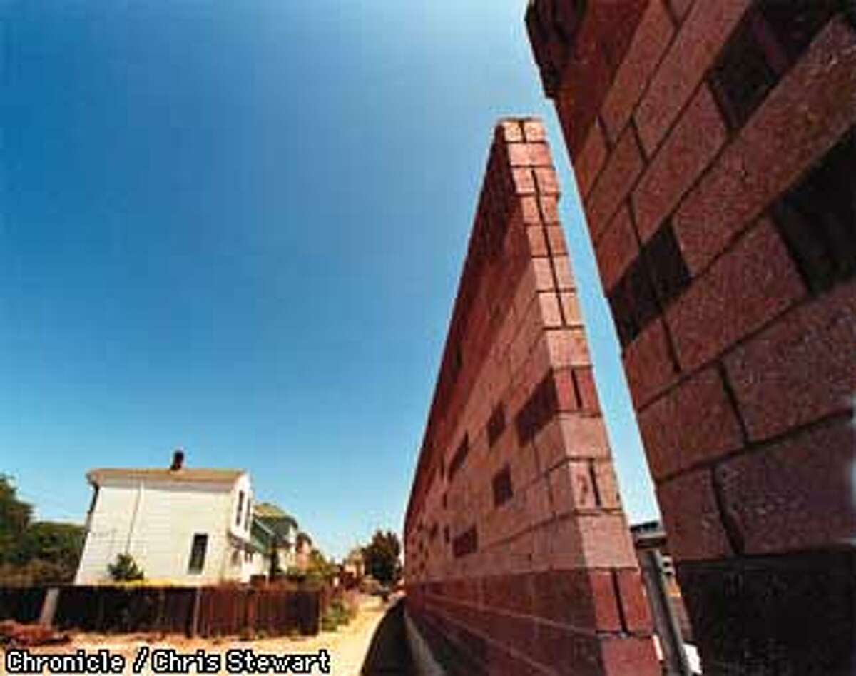 The West Oakland houses at Goss and Pine streets are dwarfed by a huge sound wall built above the soon-to-be completed Cypress freeway which was torn down following its destruction in the 1989 Loma Prieta earthquake A major portion of the rebuilt Cypress freeway should open within a month. SAN FRANCISCO CHRONICLE PHOTO BY CHRIS STEWART