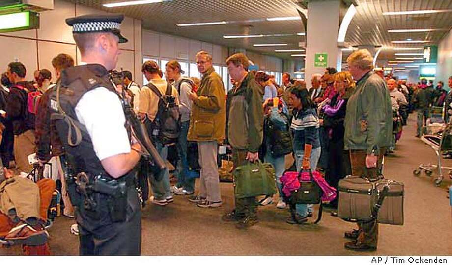 Passengers board British Airways flight BA223 watched by armed police at London Heathrow's Terminal 4, Saturday Jan. 3, 2004. British Airways flight BA223 bound for Washington Dulles airport finally took off from Heathrow airport Saturday after security fears led to its cancellation two days in a row. The 747 aircraft, carrying 225 passengers, left more than three hours late amid intense security. Police presence was high with armed officers, sniffer dogs and Land Rovers parked outside Terminal 4. (AP Photo/PA, Tim Ockenden) **UNITED KINGDOM OUT - MAGAZINES OUT - ** Photo: TIM OCKENDEN