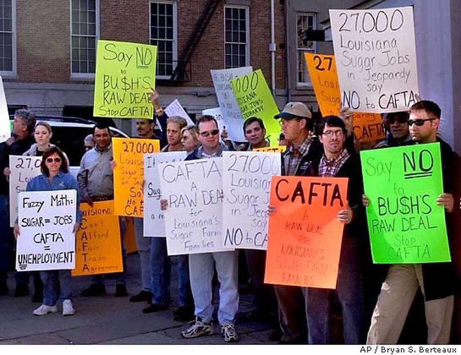 Demonstrators gathered outside the state Board of Trade building to protest CAFTA Friday, Dec. 19, 2003, during U.S. Trade Representative Robert B. Zoellick's visit to New Orleans, La. Zoellick toured the Port of New Orleans and had lunch with city and state officials. (AP Photo/The Times-Picayune, Bryan S. Berteaux) Photo: BRYAN S. BERTEAUX