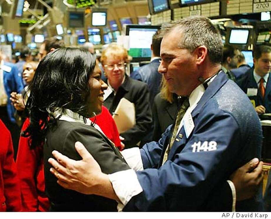 Former Iraq POW Shoshana Johnson, left, receives a warm hug from Specialist Albert Young, right, as she walks the trading floor after ringing the opening bell at the New York Stock Exchange on the last day of the year, Wednesday, Dec. 31, 2003. (AP Photo /David Karp) Photo: DAVID KARP