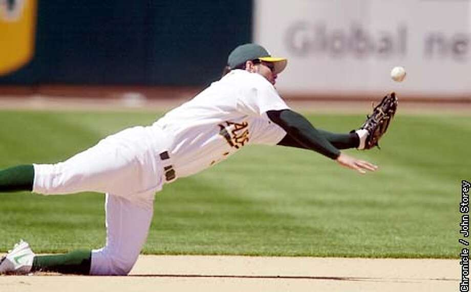ATHLETICS-C-23MAY02-SP-JRS-The A's lose to the Oriole's at the Network Coliseum. A's 3rd baseman Eric Chavez can't get Oriole's Tony Batista's hit in the 8th inning. Chronicle Photo by John Storey. Photo: John Storey