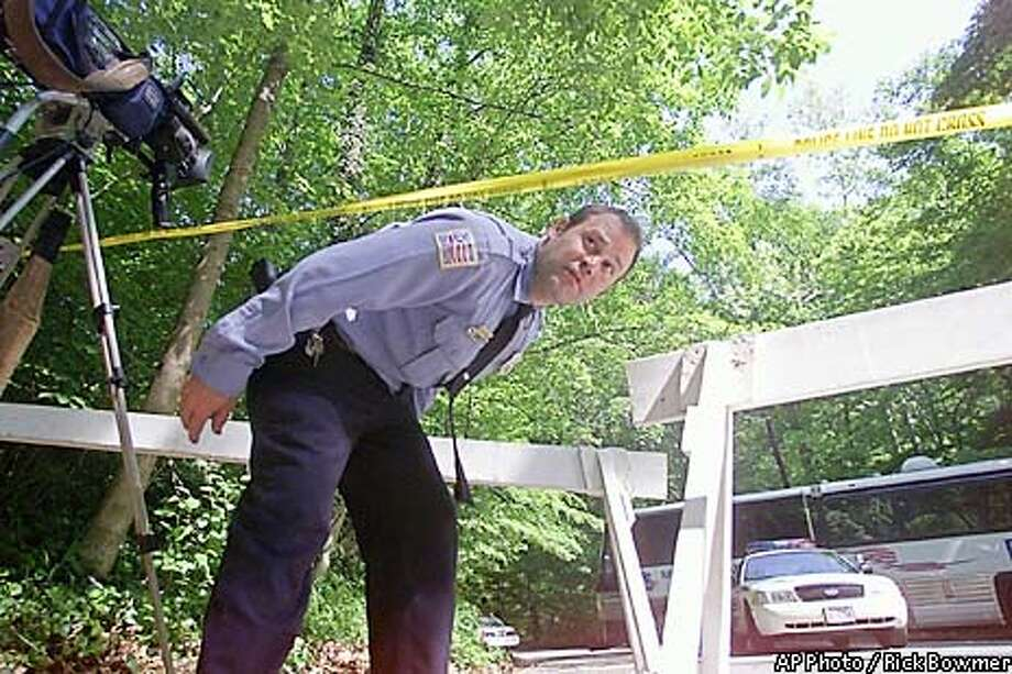A Washington police officer walks near the area in Rock Creek Park in Washington, Friday, May 24, 2002 where the remains of were found. Police resumed searching Friday for evidence about what caused Levy's death, using a device normally employed at car accidents, to try to determine how the intern's remains wound up where they were found. (AP Photo/Rick Bowmer) Photo: RICK BOWMER