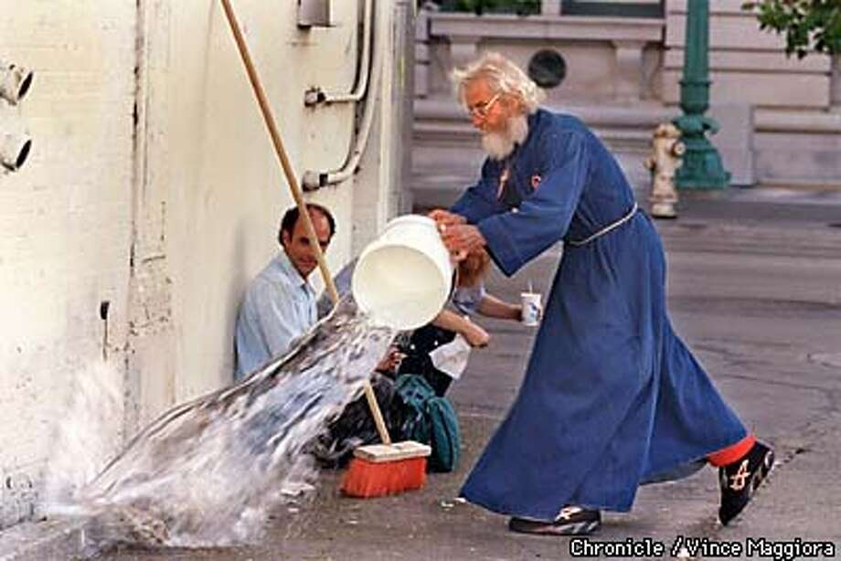 = Father Thomas Flowers washing the urine soaked wall and street with bleach and water at his food giveaway to the homeless on Jesse St. SF. by Vince Maggiora Photo: VINCE MAGGIORA