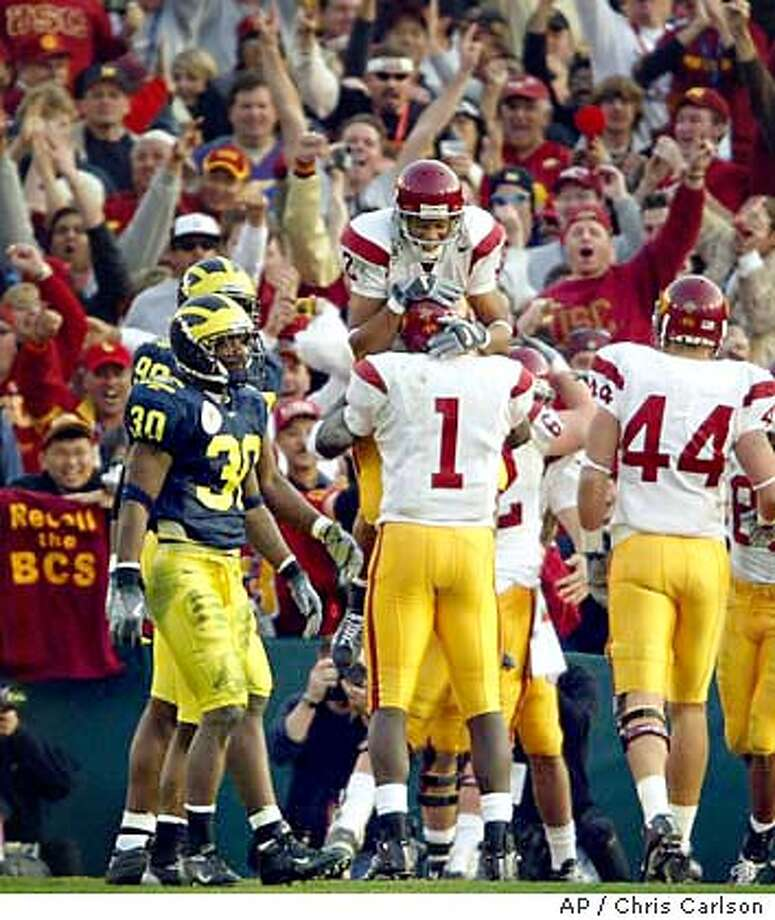 USC wide receiver Mike Williams (1) embraces teammate Steve Smith (2) as they celebrate a touchdown by Matt Leinart on a pass from Williams in the third quarter of the 90th Rose Bowl in Pasadena, Calif., Thursday, Jan. 1, 2004. Michigan's Markus Curry (30) and Pierre Woods (99) walk away at left. (AP Photo/Chris Carlson) Photo: CHRIS CARLSON