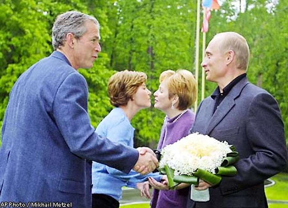 President Bush, left, and first lady Laura are welcomed by Russian President Vladimir Putin and his wife Lyudmila at the compound of their Novo-Ogarevo residence outside Moscow, Friday, May 24, 2002. (AP Photo/Mikhail Metzel, Pool) Photo: MIKHAIL METZEL