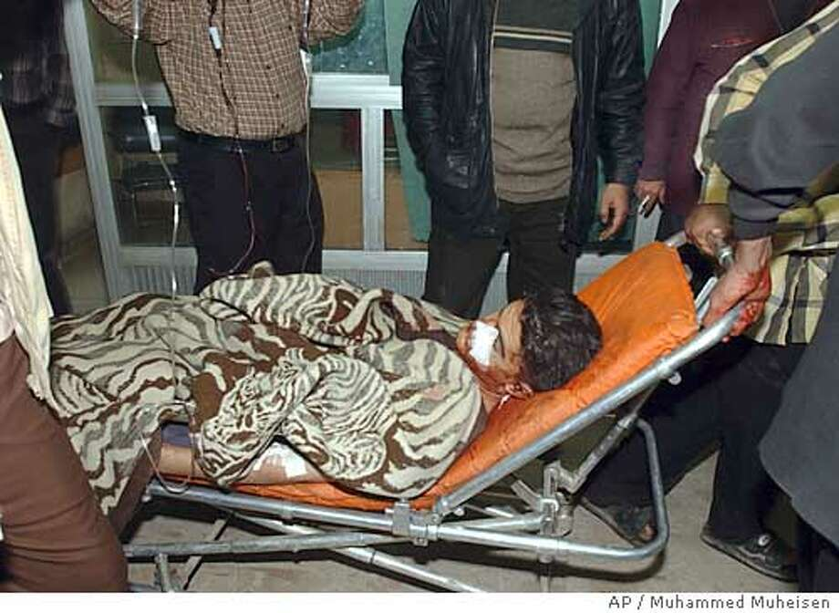 A person injured after a car bomb exploded outside a crowded restaurant in Baghdad is brought into a hospital by Iraqis, Wednesday, Dec. 31, 2003. (AP Photo/Muhammed Muheisen) Photo: MUHAMMED MUHEISEN