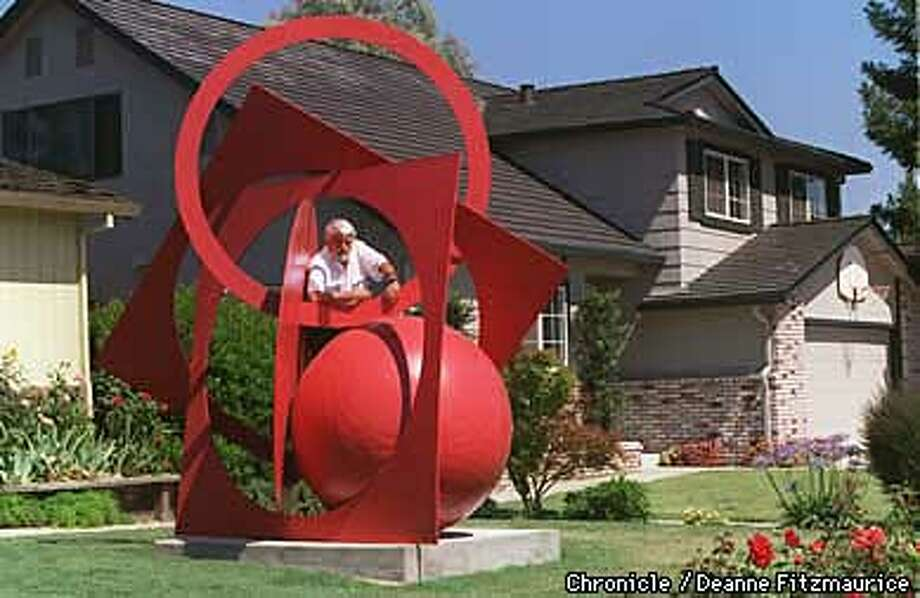Sculptor Paul Goreniuc stands with the sculpture, Space Dance for Peace, in his front yard. (his residence is at left) and the neighbors home is behind him. CHRONICLE PHOTO BY DEANNE FITZMAURICE