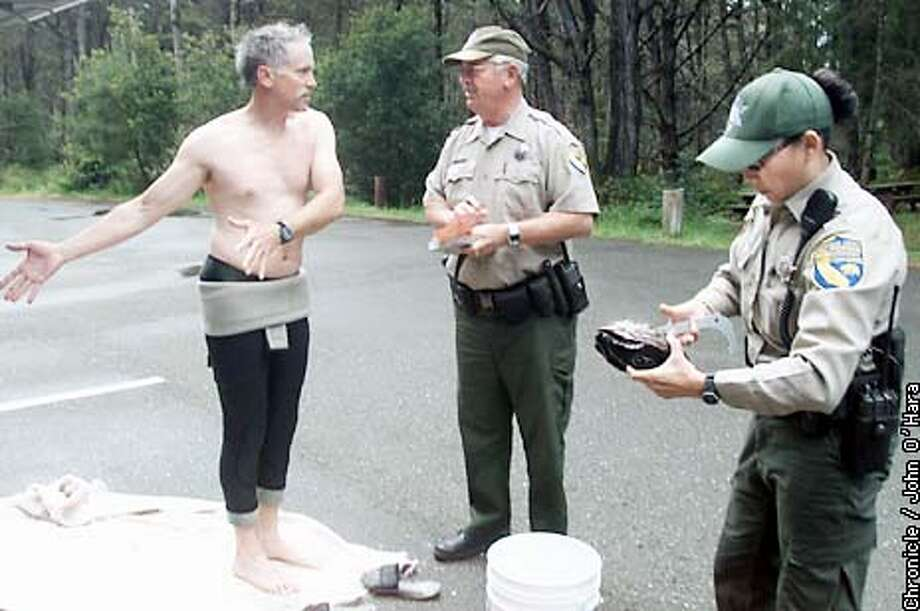 North Coast near Salt Point.  Robert Lombardi of Ashland Oregon trys to plead his case to Fish & game Warden Bob Aldrich, that this is were they go to change clothes and he would have filled out his report card then. Warden Jennifer Ikemoto measures the abalone for leagal size.  photo/John O'Hara Photo: John O'Hara