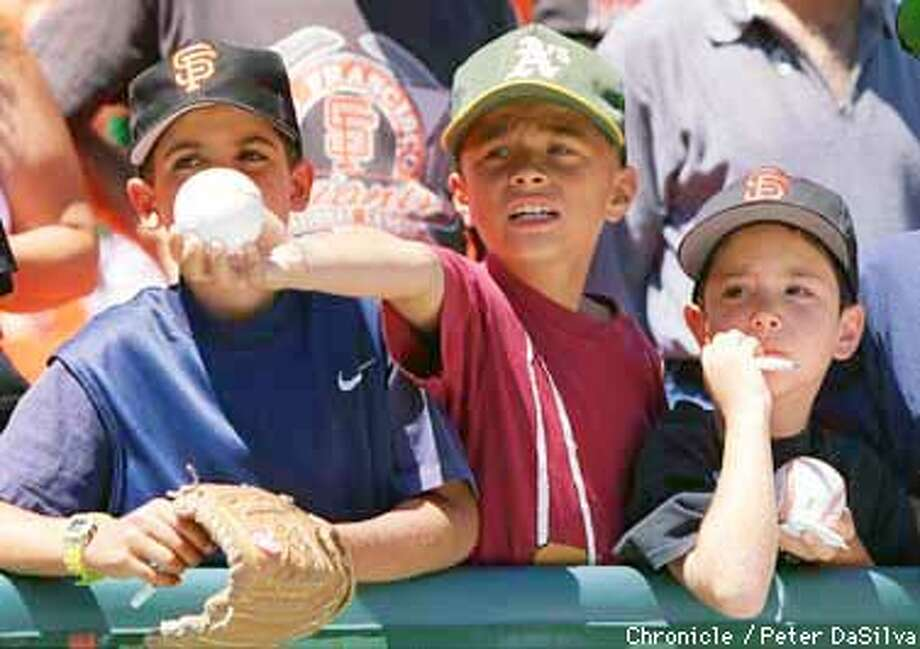 A's autograph seeker Cory Jespersen, 10 from Mountain View (center) was flanked by Giant fans Michael Burr, 10 from Windsor and Ben Gersaen, 6 of Pleasant Hill (l-r) begged for a signature before the first InterLeague Game between the Giant's and A's. Chronicle Photo By: Peter DaSilva Photo: Peter DaSilva
