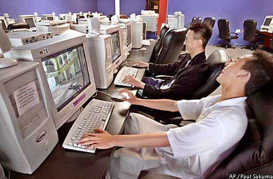 "Darren Lau, 14, right, laughs with his friend Benny Soo, 19, center, after Lau was defeated by Soo in the game ""Counter-Strike"" played online at a computer gaming store, ""Cyber Hunt"" in San Francisco that specializes in online computer gaming, Monday, May 20, 2002. Playing costs $4.00 per hour. The video game industry is revving up its online offerings this week after a flurry of console price cuts. The big three machine makers _ Microsoft, Sony and Nintendo _ are banking on people's willingness to pay subscription fees for multiplayer interactive games as high-speed Internet access becomes more available. (AP Photo/Paul Sakuma) Photo: PAUL SAKUMA"