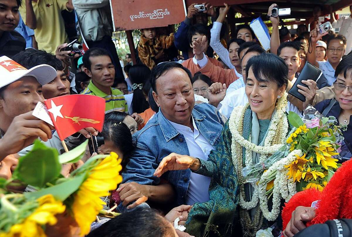 Myanmar opposition leader Aung San Suu Kyi (R) is greeted by supporters as she arrives to address a gathering as part of her campaign trail on the outskirts of Myanmar's southern city of Dawei on January 29, 2012. Huge crowds lined the streets to greet Suu Kyi as she hit the campaign trail on January 29 ahead of by-elections seen as a key test of the regime's commitment to reform. AFP PHOTO/Soe Than WIN (Photo credit should read Soe Than WIN/AFP/Getty Images)