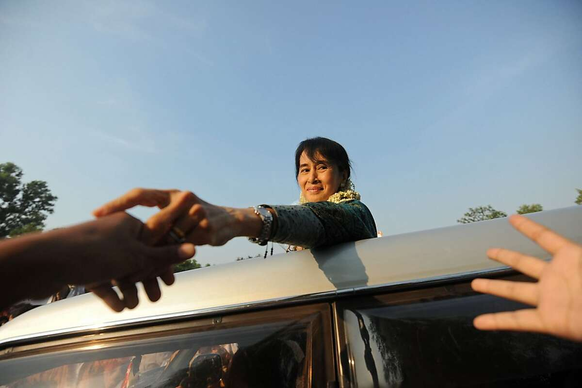 TOPSHOTS Myanmar's opposition leader Aung San Suu Kyi greets supporters upon her arrival in Myanmar's southern city of Dawei on January 29, 2012. Suu Kyi traveled on the campaign trail to Dawei on January 29 to promote her party ahead of April's by-elections. Nobel Peace Prize winner Suu Kyi is standing for office in the polls after spending much of the past two decades in detention. AFP PHOTO/Soe Than WIN (Photo credit should read Soe Than WIN/AFP/Getty Images)